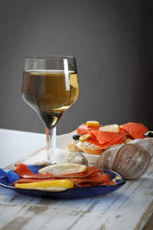 king salmon: Tasty various italian sandwiches with seafood against rustic wooden background. Crostini with cheese, red fish and olives on white plate and wine, close up with selective focus Stock Photo