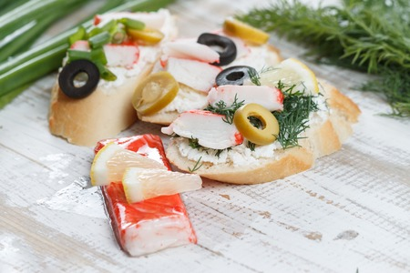 king salmon: Tasty various italian sandwiches with seafood against rustic wooden background. Crostini with cheese, crab sticks, olives, and herbs, horizontal view with selective focus