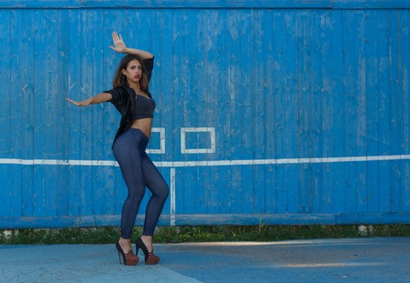 suntanned: Young sexy suntanned woman in a short top, shirt and leggins on high heels with beautiful modern make-up and hair dancing against blue painted wooden wall with copy space, horizontal view