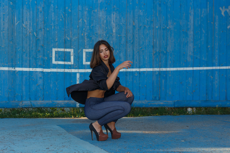 Young sexy suntanned woman in a short top, shirt and leggins on high heels with beautiful modern make-up and hair dancing against blue painted wooden wall with copy space, horizontal view