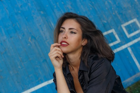 suntanned: Young sexy suntanned woman in a short top and shirt with beautiful modern make-up and hair posing against blue painted wooden wall, portrait with copy space, horizontal view