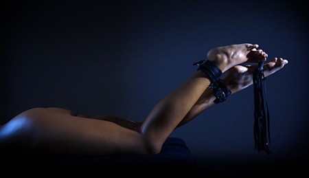 Low key photo of sexy female nude legs binded with cuffs holding whip against dark background, horizontal view