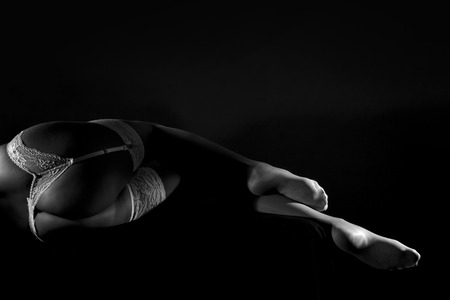 Low key greyscale photo of long beautiful sexy female legs in white stockings and belt, hands in gloves against dark background, h