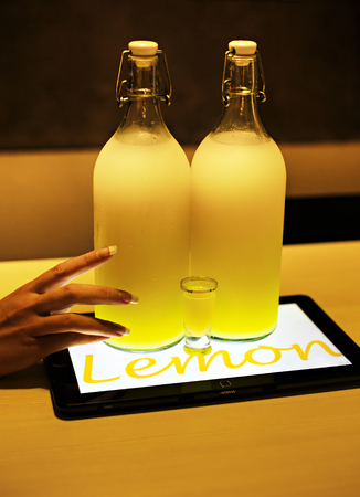 ambient light: Lemoncello cocktail in two big bottles and small shot glass on table lighted by tablet underneath in cafe, female hand holding bottle, ambient light photo Stock Photo