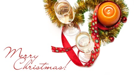 Merry Christmas greeting card made of two glasses of champagne, yellow and green tinsel with red christmas balls, red ribbon with snowflakes and orange candle with chinese hieroglyph for rooster, horizontal top view