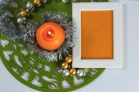 Merry Christmas and New Year greeting card on green christmas mat, silver tinsel with silver and golden christmas balls and orange candle against white background, horizontal top view