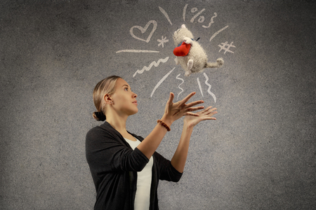 tosses: Young beautiful blond woman tosses plush toy cat with plush heart. Doodle sketch is drawn on grey texture background. Holiday gift concept with copy space