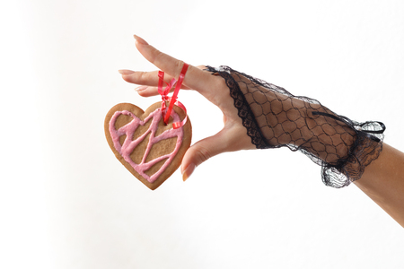 One beautiful female hand in black lace glove holds a heart shaped gingerbread cookie on red ribbon against white beackground, horizontal view. Valentines day and love concept Stock Photo
