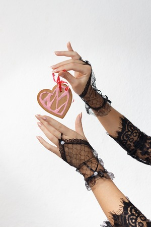 lace gloves: Two beautiful female hands in black lace gloves hold a heart shaped gingerbread cookie on red ribbon against white beackground. Valentines day and love concept
