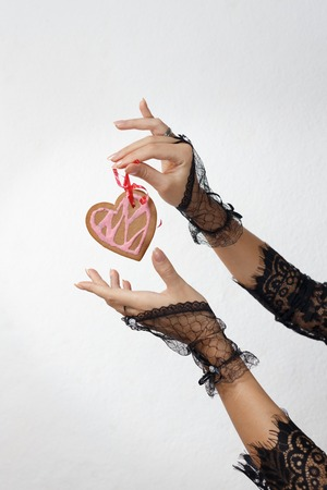 Two beautiful female hands in black lace gloves hold a heart shaped gingerbread cookie on red ribbon against white beackground. Valentines day and love concept