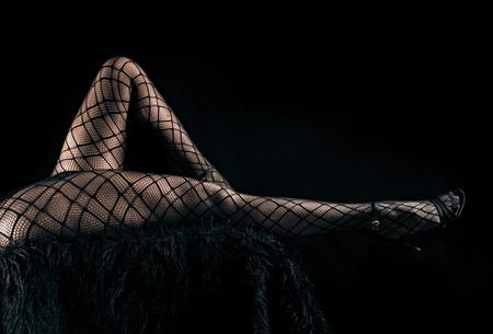 Rustige foto van sexy slanke mooie benen in zwarte netto legging en hoge hielschoenen die op bont tegen zwarte achtergrond, horizontale mening liggen