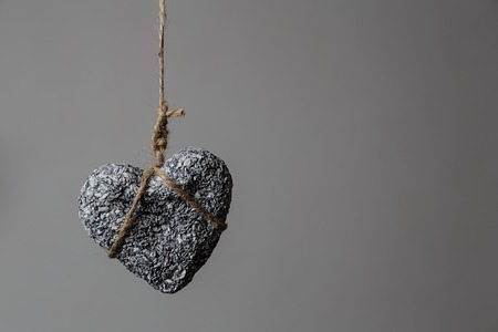 Stone heart in jute bondage hangs against grey background with copy space, Valentines day concept, horizontal view