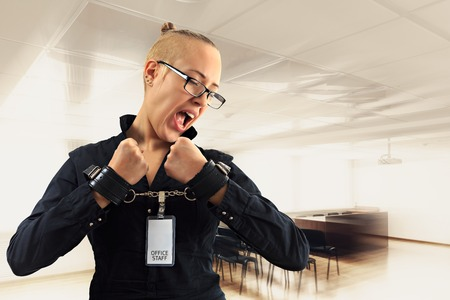 trouble free: Young beautiful businesswoman screaming with anger in office, prisoner of job in cuffs, horizontal view