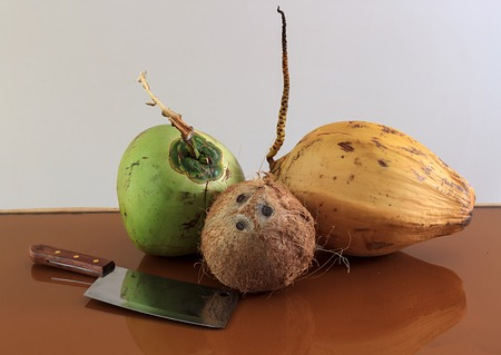 three different coconuts with machete on table horizontal view