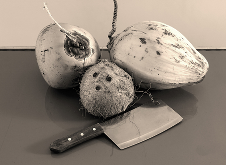 three different coconuts with machete on table horizontal view, greyscale photo