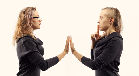psychics: Self talk concept. Young blond caucasian woman talking to herself, showing gestures. Double portrait from two different side views. Stock Photo