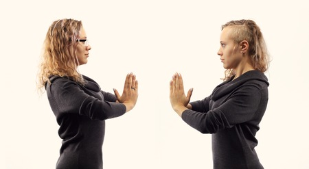 psychics: Part of series.Self talk concept. Young blond caucasian woman talking to herself, showing gestures. Double portrait from two different side views.