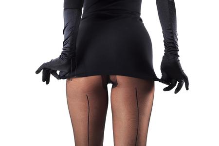 Jambes féminines sexy en beaux bas élégants et chaussures à talons hauts, gants noirs et robe isolé sur fond blanc, vue horizontale
