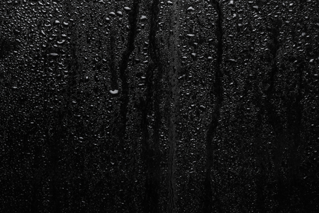 Part of series. Background photo of rain drops on dark glass, different size: small medium and large, horizontal view