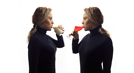 Part of series. Self talk concept. Portrait of young woman talking to herself in mirror, drinking milk or wine in glass. Double portrait