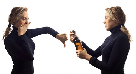 disapprove: Part of series. Self talk concept. Portrait of young woman talking to herself in mirror, offering beer in bottle, disapproving in reply. Double portrait Stock Photo