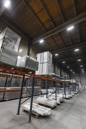 Generic warehouse industrial interior with palettes stacked on shelves. Wide angle perspective view