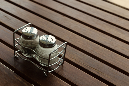 angled view of salt and pepper dispensers upon wooden table
