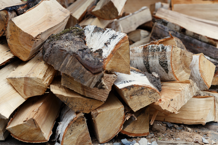 Closeup of fresh chopped birch firewood on a pile. A concept of natural heating resource