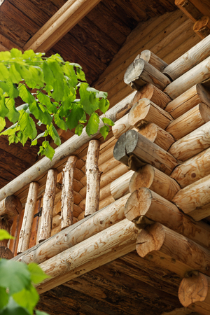 Traditional Russian wooden construction, the balcony of the house with logs, round bars on the wall of the house, the ends of felled beams.