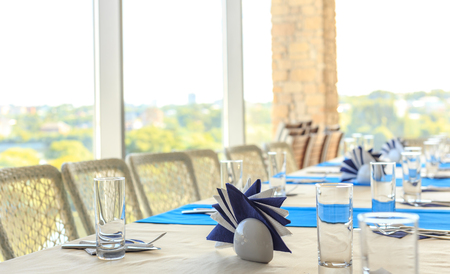 Empty half-served banquet table in restaurant with napkins, glasses, forks, knives, shallow DOF view against blurred city skyline background Empty half-served banquet table in restaurant with napkins, glasses, forks, knives, shallow DOF view against blurred city skyline