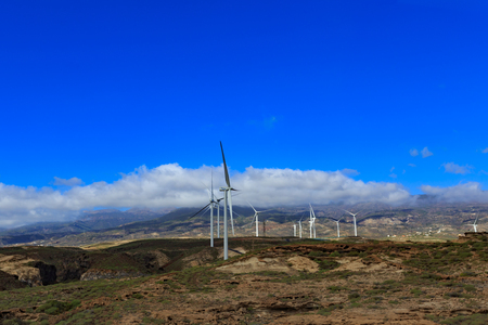 TENERIFE, SPAIN - NOVEMBER 2018: Group of windmills for electric power production in front of the mountains in Tenerife, Spain