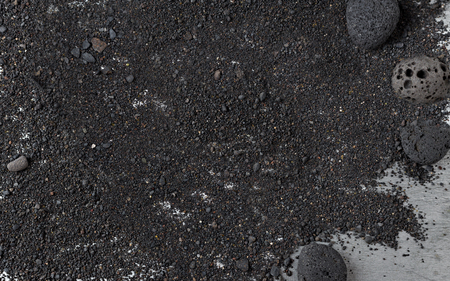 Black volcanic sand background with round lava rocks
