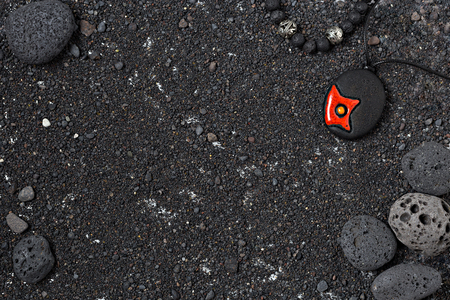 Black volcanic sand background with round lava rocks