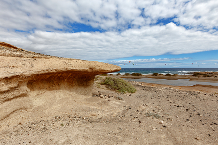 Kite surfers behind the cliff on El Medano beach, Tenerife, Spain Reklamní fotografie
