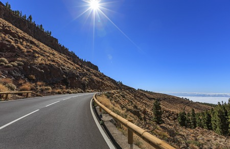 Winding mountain road against the sun in daytime, one of the most dangerous asphalt roads in Tenerife, Spain Standard-Bild