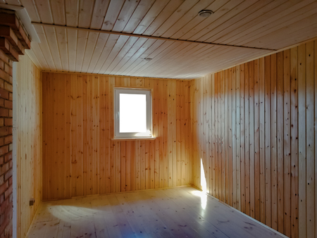 Empty new living room in a wooden countryhouse. Wooden walls and parquet flooring