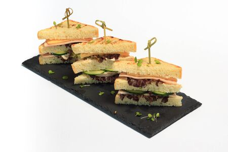 triangle club sandwich tripple set on black ceramic plate part of series Stock Photo