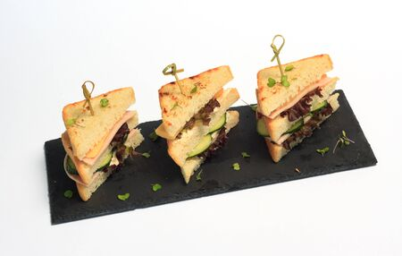 triangle club sandwich tripple set on black ceramic plate part of series Standard-Bild