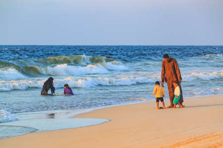 EL AGAMY, ALEXANDRIA, EGYPT - CIRCA OCTOBER 2014 - undefined egyptian family enjoy Mediterrenian beach at sunset Editorial
