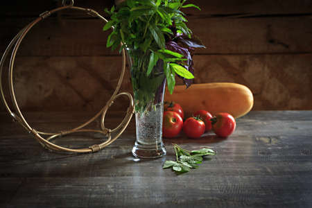 Summer still life of fresh mint and sweet basil in front of tomatoes and marrow on rustic background