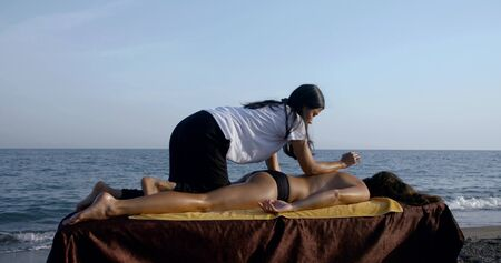 female client is relaxing during procedure of traditional thai massage on sea coast in summer day Imagens