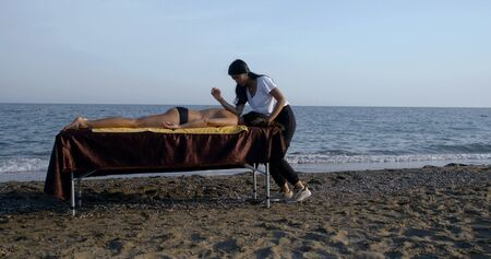 thai female master is massaging back of woman patient lying on massage table on sea shore