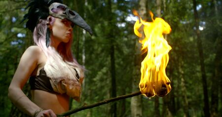 female shaman is holding burning torch in hand, standing in forest, preparing to ritual