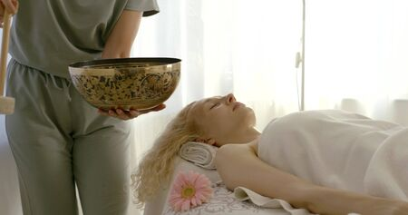 therapist is holding vibrating tibetan bowl near woman lying on table, masseur is stroking her hand Imagens