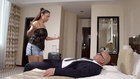 Rico hombre de negocios en un traje acostado en la cama en el hotel mirando a su amante, un pasatiempo de placer