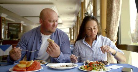 nice couple enjoys eating salads sitting near window in cafe