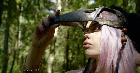 shaman with long purple hair takes off bone mask and looks Фото со стока