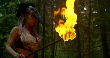 woman in costume with mask on head holds burning torch