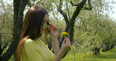 Close-up portrait of a young beautiful girl with long dark hair standing in nature on a background of trees. Shes wearing sunglasses that reflect. In her hands she holds a yellow dandelion.