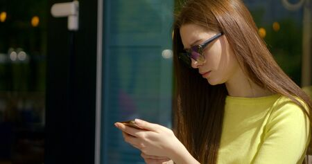 brunette in pullover and sunglasses types on smartphone Stok Fotoğraf